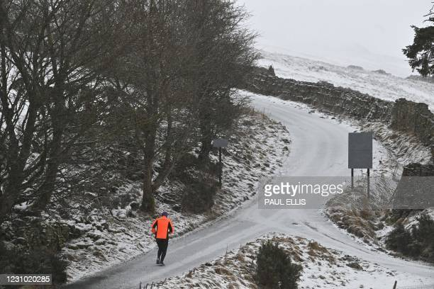 Runner is seen on a lane in the snow in Askrigg, northern England, on February 7, 2021. - Cold weather swept across northern Europe bring snow and...