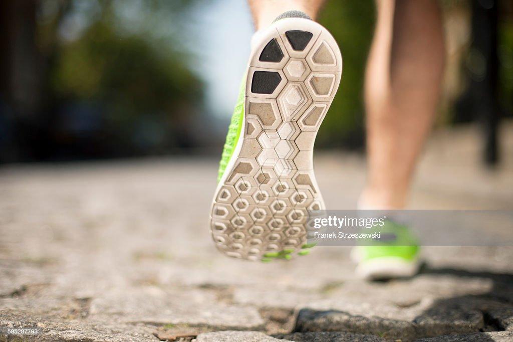 Runner jogging on cobbled street : Stock Photo