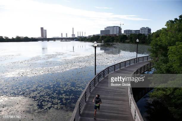Runner jogs along a Mystic River Reservation footbridge at Sylvester Baxter Park in Somerville, MA on Aug. 3, 2020.