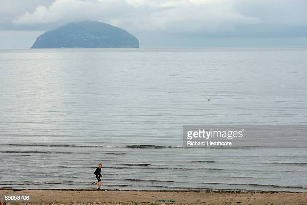 A runner jogs along the beach in front of Ailsa Craig during round one of the 138th Open Championship on the Ailsa Course Turnberry Golf Club on July...