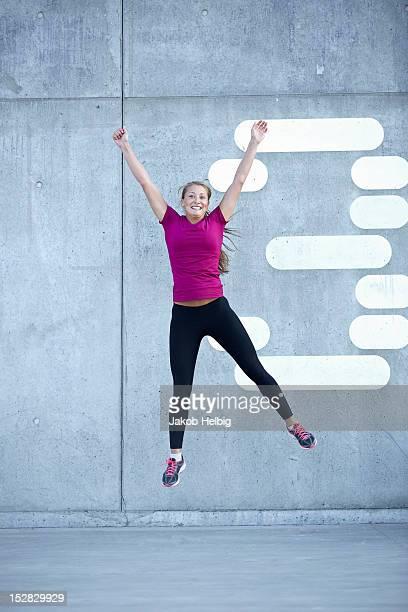 Runner jumping for joy on city street