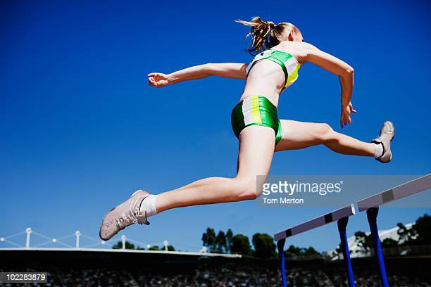 Runner jumping hurdles on track