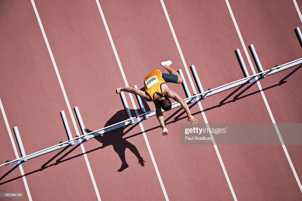 Runner jumping hurdles on track : Stock Photo