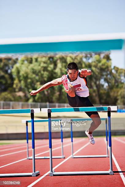 runner jumping hurdles on track - hurdling stock photos and pictures