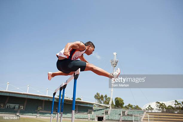runner jumping hurdles on track - hurdling track event stock pictures, royalty-free photos & images