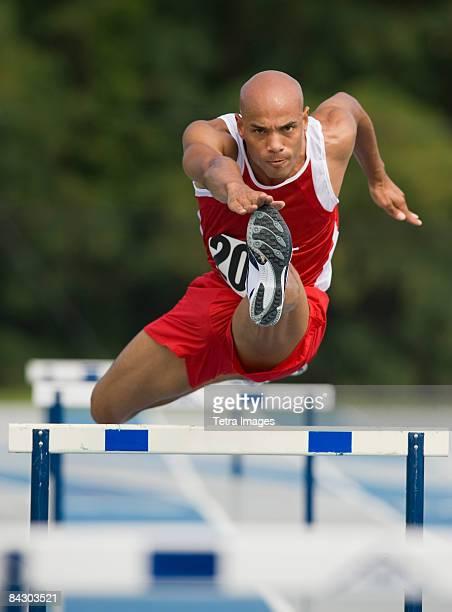 Runner jumping over hurdle