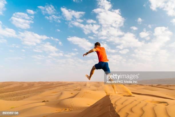 Runner jumps off dune in desert