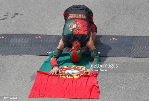 A runner lays down on a Portuguese flag after crossing the finish line of the 123rd Boston Marathon on April 15 2019