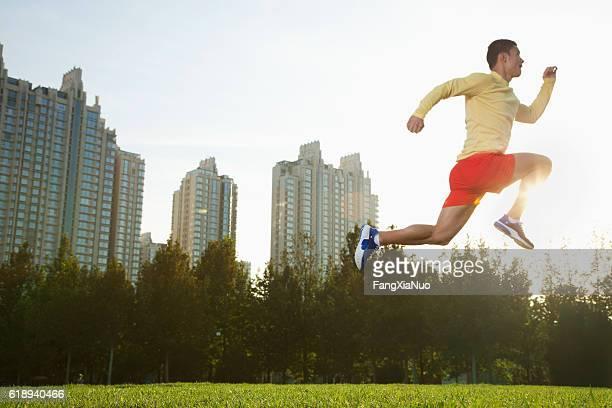 Runner leaping in park