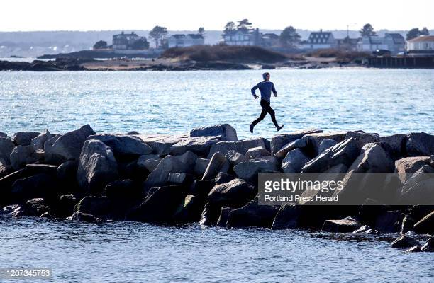 Runner leaps over the boulders at the breakwater on Goochs Beach in Kennebunk on March 1, 2019.