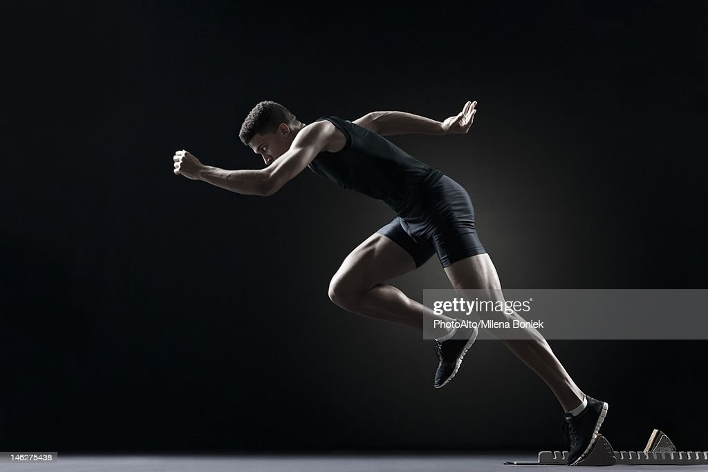 Runner leaving starting block : Stock Photo