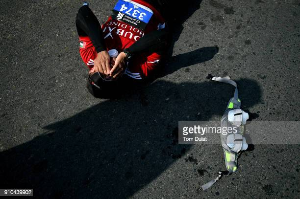 A runner lies on the road after finishing the Standard Chartered Dubai Marathon on January 26 2018 in Dubai United Arab Emirates