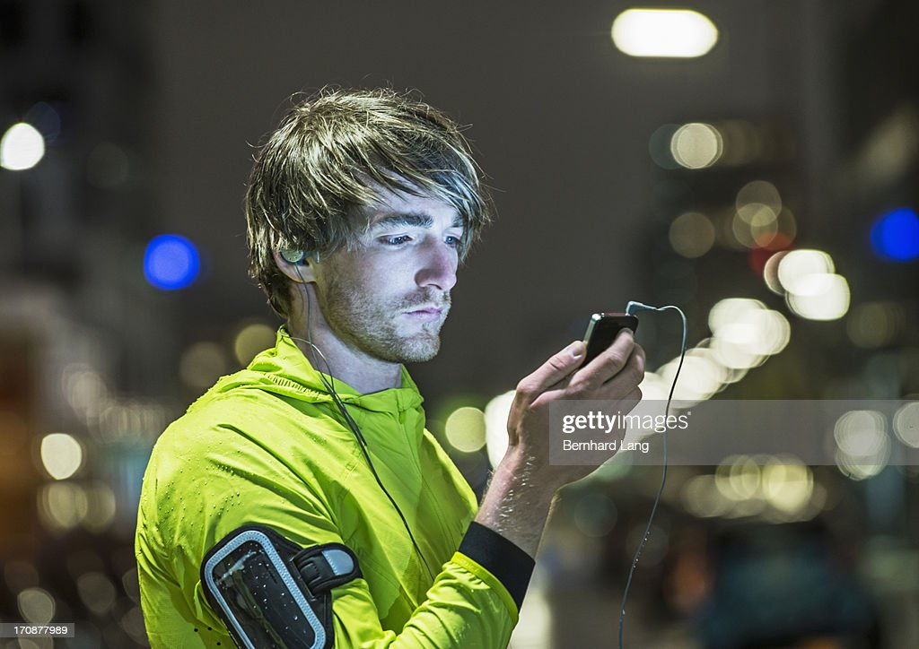 Runner looking on smartphone in city by night : Stock Photo
