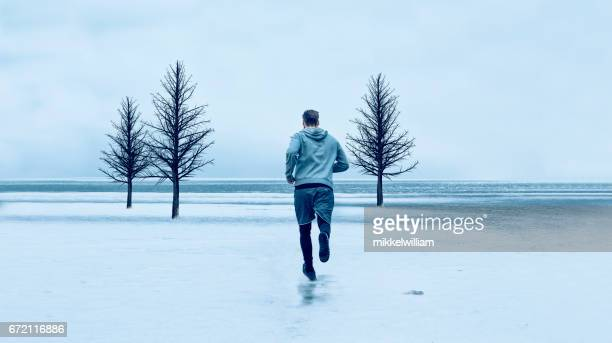 Runner makes his way out on a icy road near the sea