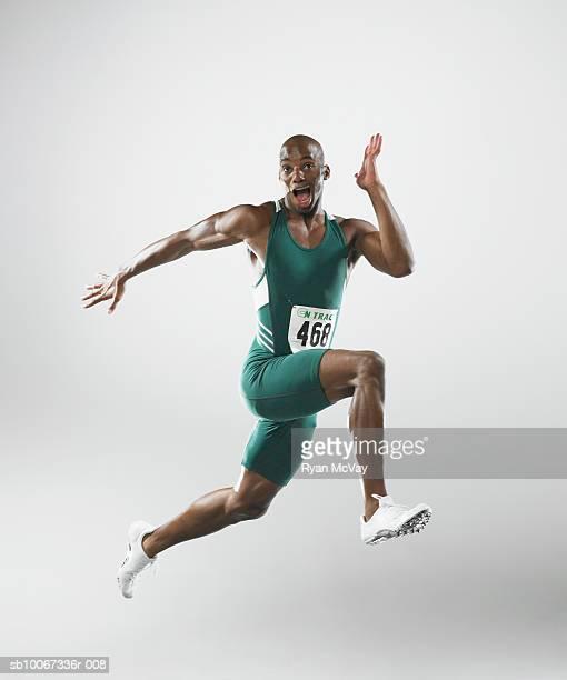 Runner making face in mid-stride (studio shot)