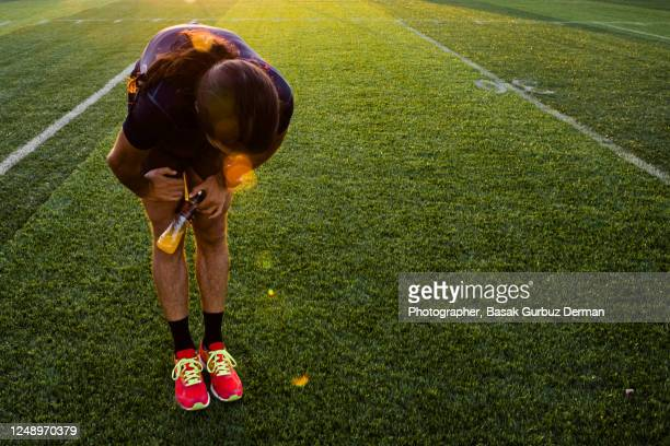 a runner man feeling exhausted after exercise, holding his knees, on a hot day, holding a bottle of sports nutrition drink - extra long stock pictures, royalty-free photos & images