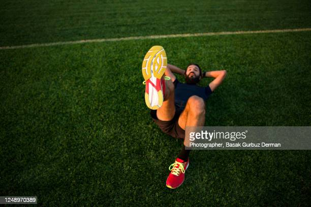 a runner man lying on the artificial grass field of a running track, holding one of his feet up - extra long stock pictures, royalty-free photos & images