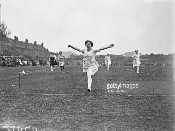 Runner Miss Lucas celebrates as she crosses the line in first place at an unspecified athletics meeting in Hendon, London, England, June 1921.