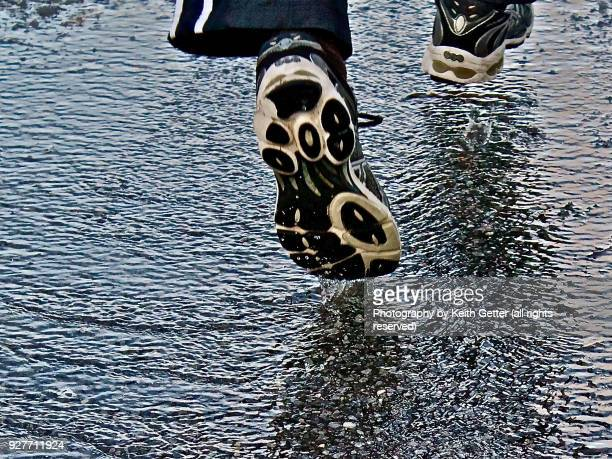 a runner nearly in mid-air striding above flowing water on a blacktop pathway with close-up of splashing droplets - striding stock pictures, royalty-free photos & images