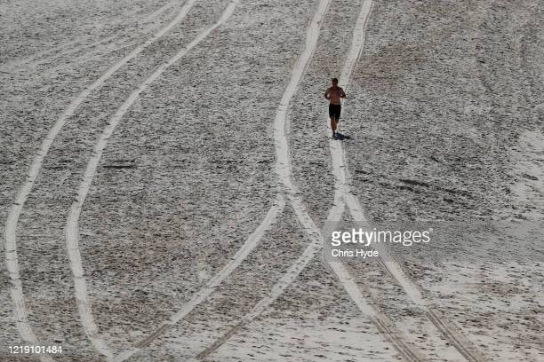 A runner on Mermaid beach on April 16 2020 in Gold Coast Australia The Federal Government has closed all nonessential business and implemented strict...