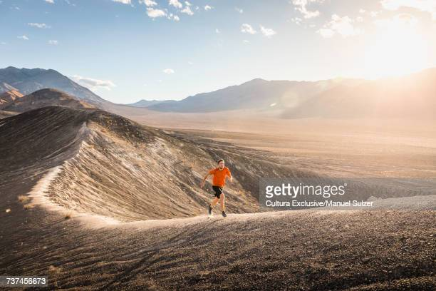 Runner on ridge of Ubehebe Crater, Death Valley National Park, Furnace Creek, California, USA