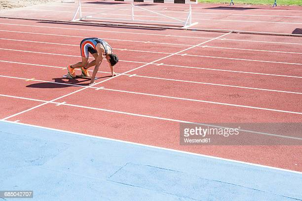runner on tartan track in starting position - track and field stadium stock pictures, royalty-free photos & images