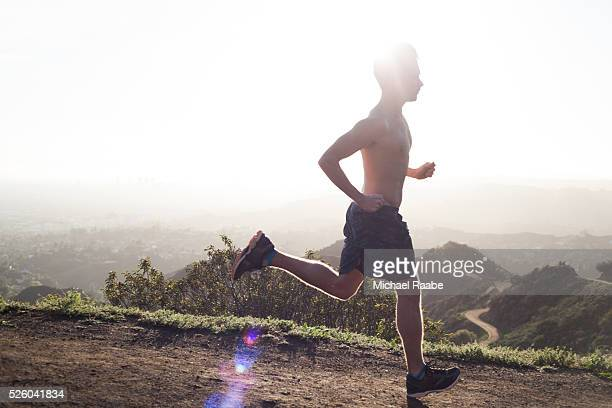 Runner on trail with sun behind him