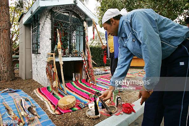 Runner Oscar Paredas picks up a religious object to carry for the day while morning prayers and Native American cleansing ceremonies are performed as...