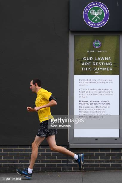 A runner passes a sign saying 'Our Lawns are resting this summer' at The All England Tennis and Croquet Club on June 29 2020 in Wimbledon England The...