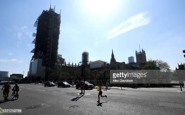 A runner passes Big Ben and the Houses of Parliament on April 26 2020 in London England The 40th London Marathon was due to take place today with...