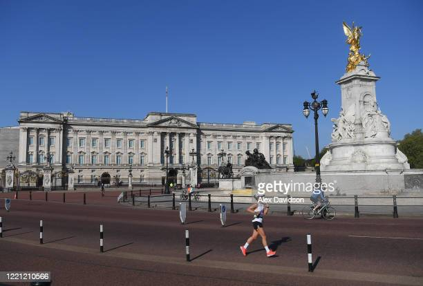A runner passes Buckingham Palace on April 26 2020 in London England The 40th London Marathon was due to take place today with thousands of runners...