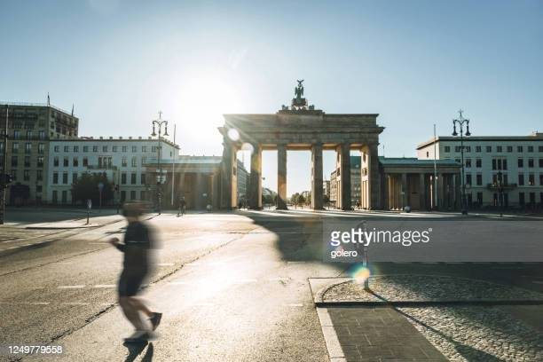 runner passing in front of brandenbuger tor in berlin in the morning light - city gate stock pictures, royalty-free photos & images