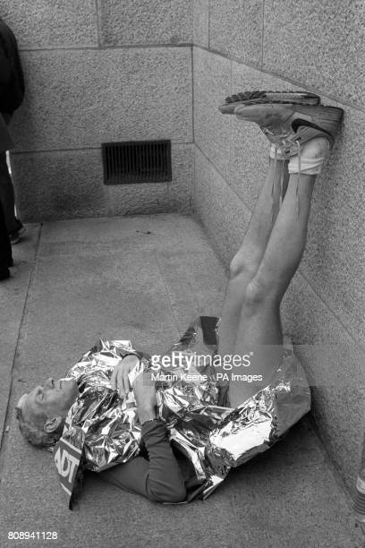 A runner puts his feet up against a wall after finishing the Marathon