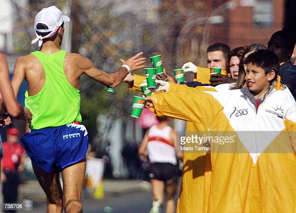 A runner reaches for water as he passes through the borough of Queens November 4 2001 during the 32nd New York City Marathon Security concerns...