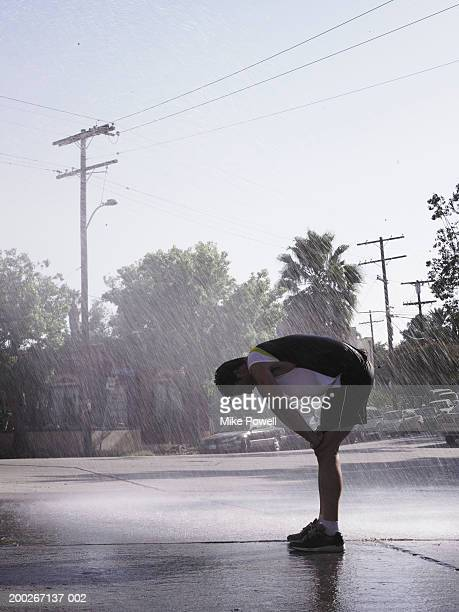 runner resting in water sprinkles on street - hand on knee stock pictures, royalty-free photos & images