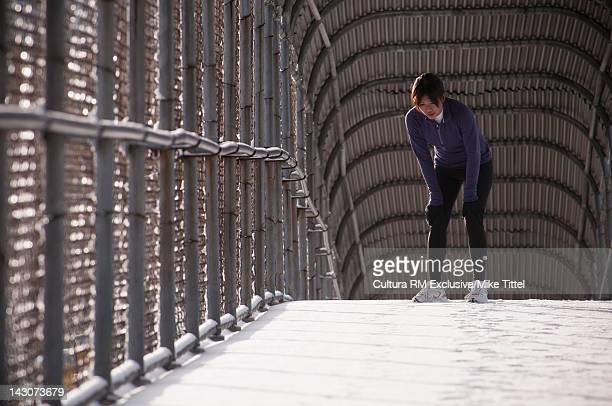 Runner resting on urban walkway