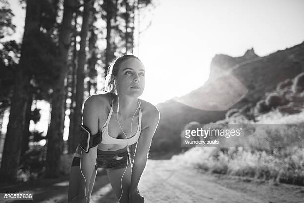 Runner resting with hands on her knees on nature trail