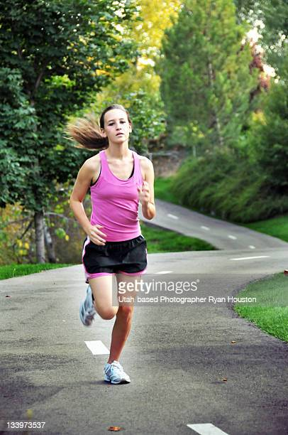 Runner running down curved path in Urban Park