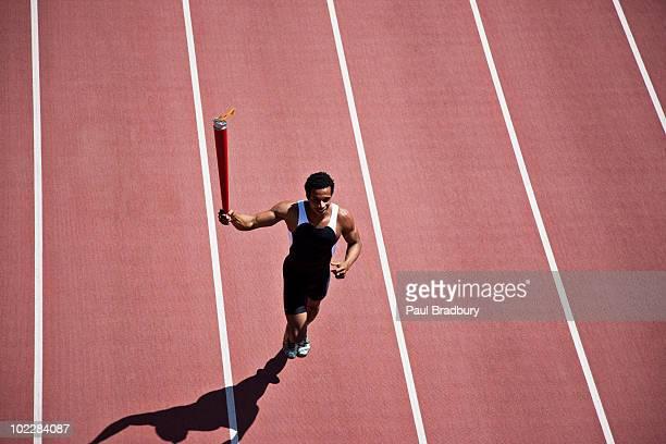 Läufer laufen mit Fackel am track