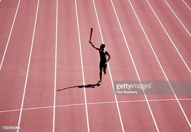 runner running with torch on track - lap of honour stock pictures, royalty-free photos & images