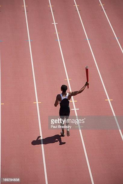 runner running with torch on track - olympische spelen stockfoto's en -beelden