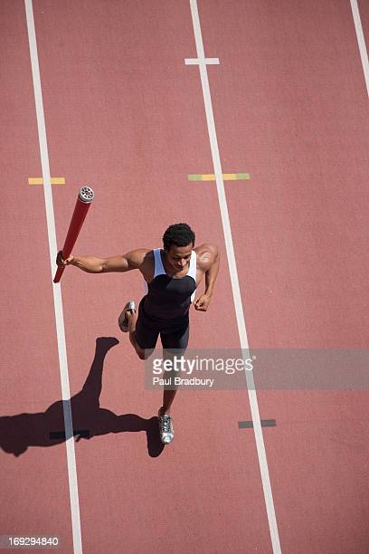 runner running with torch on track - the olympic games stock pictures, royalty-free photos & images