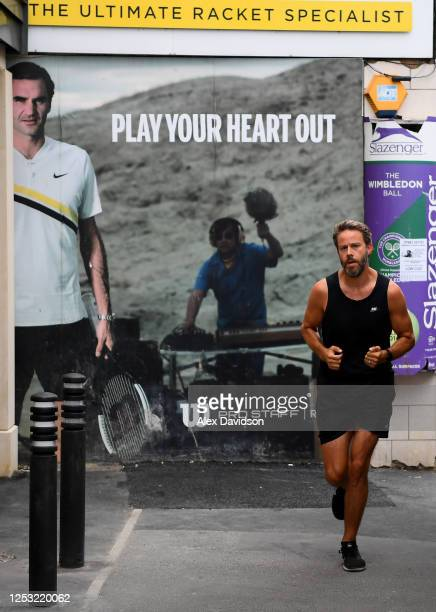 A runner runs past a Tennis Racket shop on June 29 2020 in Wimbledon England The Wimbledon Tennis Championships were due to start today but were...