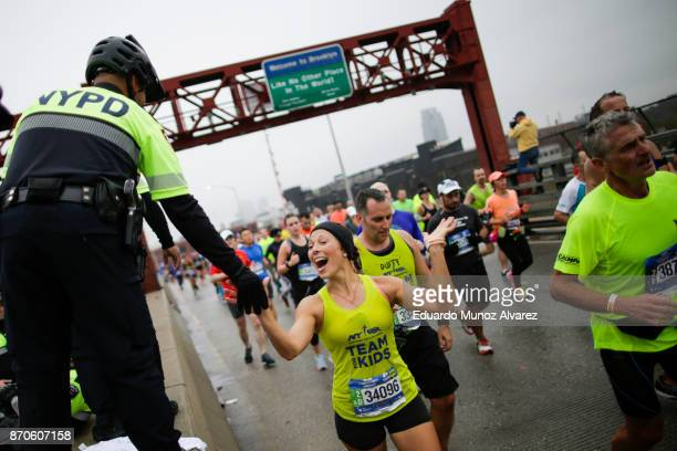 A runner shakes hands with a NYPD officer as they cross the Pulaski Bridge from Brooklyn into Queens during 2017 TCS New York City Marathon November...