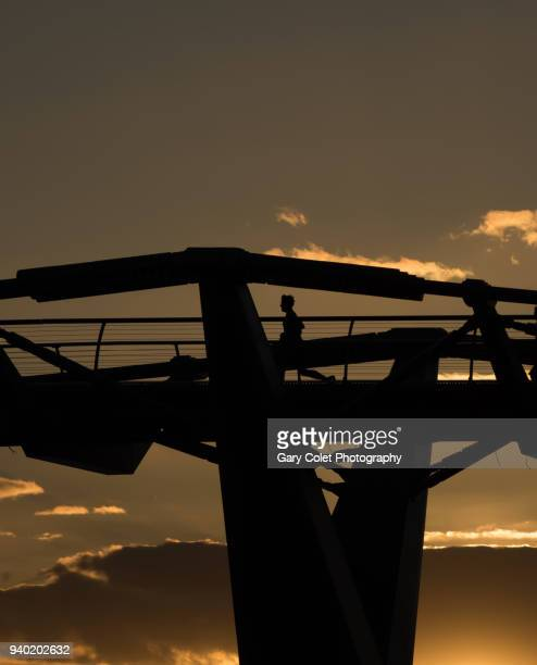 runner silhouetted on millennium bridge - gary colet stock pictures, royalty-free photos & images