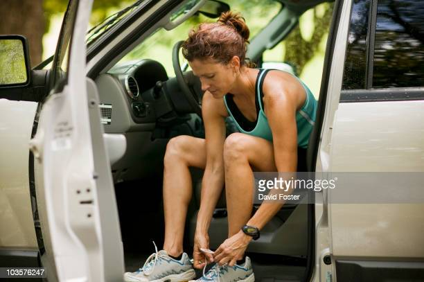 Runner sitting in car tying shoes