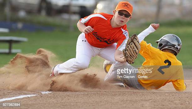 Runner slides into third base during the Norwalk Little League baseball competition at Broad River Fields, Norwalk, Connecticut. USA. Photo Tim...