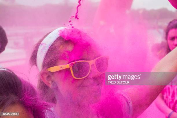 A runner smiles as she's sprayed with purple powder during the Color Run race in Paris on April 13 2014 The Color Run is a five kilometres paint race...