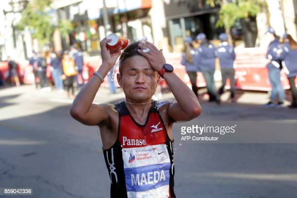A runner splashes water in his face as he participates in the Chicago Marathon on October 8 2017 in Chicago Illinois / AFP PHOTO / Joshua Lott