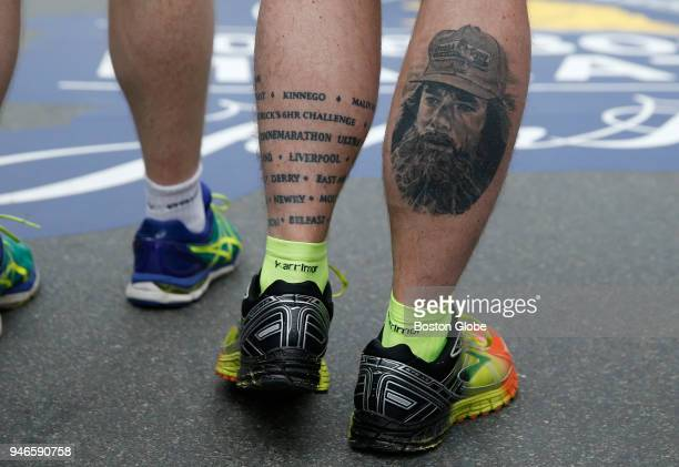 A runner sports a tattoo of Forrest Gump beside a list of marathons as he stands at the finish line of the Boston Marathon in Boston MA on April 15...